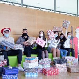 Weihnachten im Schuhkarton - Schüler halten Weihnachtspäckchen hoch